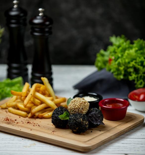 Weiße und schwarze sesambällchen mit pommes frites auf holzbrett Kostenlose Fotos