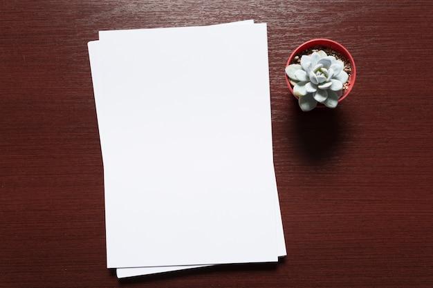 Weiße visitenkarte auf holztisch. leeres porträt a4. Premium Fotos