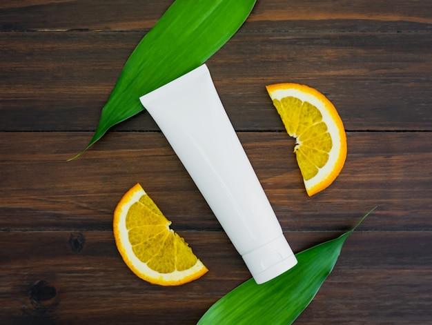Weiße vitamin c-flasche und öl aus orangenfruchtextrakt, modell der beauty-marke in flachlage Premium Fotos