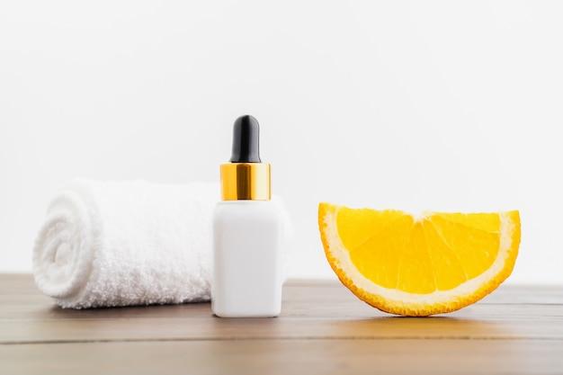 Weiße vitamin c flasche und öl aus orangenfruchtextrakt, modell der beauty-produktmarke. draufsicht über den hölzernen hintergrund. Premium Fotos