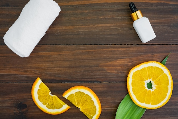 Weiße vitamin c flasche und öl aus orangenfruchtextrakt, modell der beauty-produktmarke. Premium Fotos