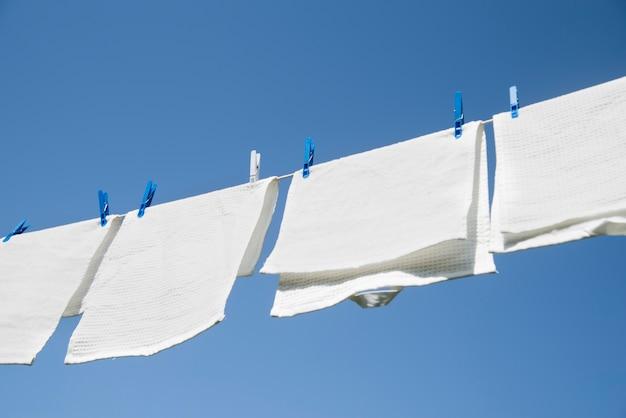 Weiße wäsche, die draußen an einer schnur hängt Kostenlose Fotos