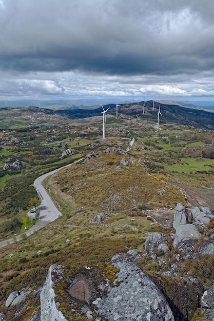 Weiße windturbinen auf einem großen grünland Kostenlose Fotos