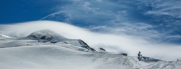 Weiße winterberge bedeckt mit schnee im blauen bewölkten himmel. alpen. österreich. pitztaler gletscher Premium Fotos
