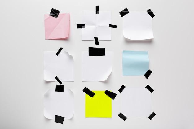 Weiße zerrissene anmerkung, notizbuchpapier fest mit dem schwarzen klebeband lokalisiert auf weißem hintergrund Premium Fotos