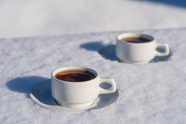 Weiße zwei tasse heißen kaffees auf einem bett aus schnee und weißem hintergrund, nah oben. konzept des weihnachtswintermorgens Premium Fotos