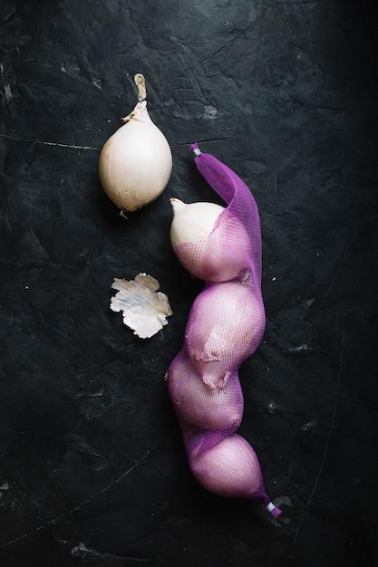 Weiße zwiebeln der draufsicht auf einem gemüsenetz Kostenlose Fotos