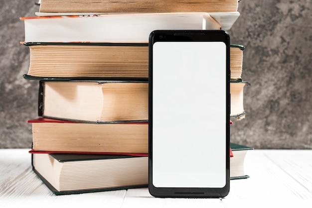 Weißer anzeigenhandy des leeren bildschirms vor buch gestapelt auf tabelle Kostenlose Fotos