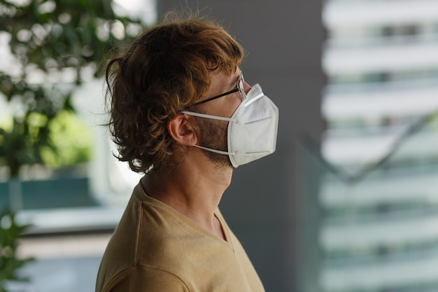 Weißer bärtiger erwachsener mann, der chirurgische maske auf einer industriellen wand trägt. gesundheit, epidemien, soziale medien. Kostenlose Fotos