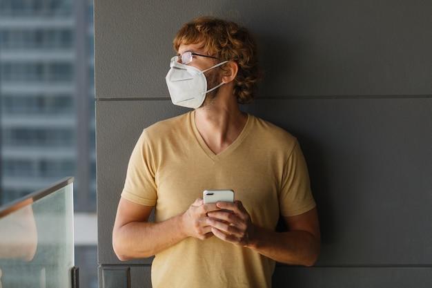 Weißer bärtiger erwachsener mann, der smartphone beim tragen der chirurgischen maske auf einer industriellen wand verwendet. gesundheit, epidemien, soziale medien. Kostenlose Fotos