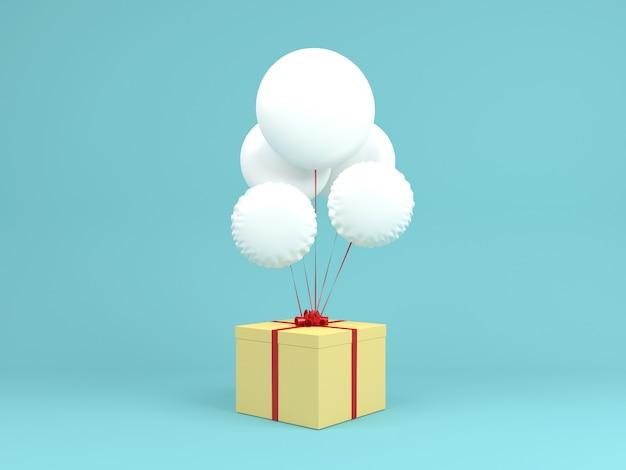 Weißer ballon mit gelber geschenkbox auf blauem pastellhintergrund Premium Fotos