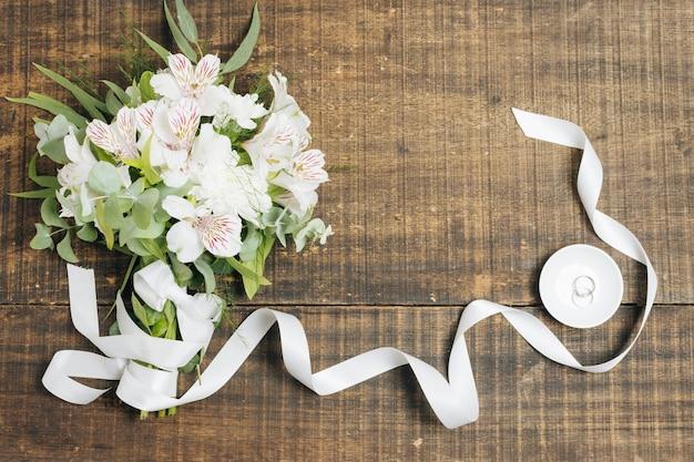 Weißer band- und blumenblumenstrauß mit eheringen auf platte über hölzernem schreibtisch Kostenlose Fotos