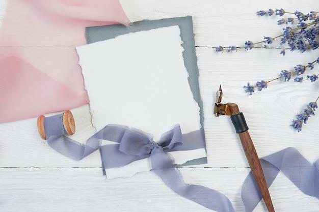 Weißer bandbogen der leeren karte auf einem hintergrund des rosa und blauen gewebes mit lavendelblumen und kalligraphischem stift Premium Fotos