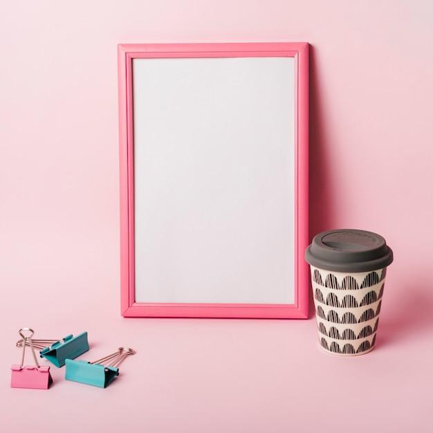 wei er bilderrahmen mit rand b roklammern und kaffee einwegbecher vor rosa hintergrund. Black Bedroom Furniture Sets. Home Design Ideas
