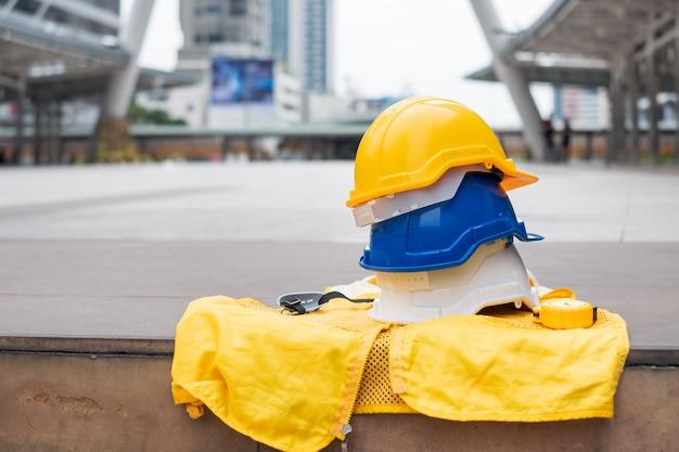 Weißer, blauer und gelber schutzhelm mit formeller weste für arbeitssicherheitsarbeiter Premium Fotos