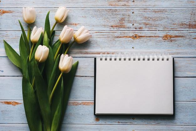 Weißer blumenstrauß von tulpen auf einem holztisch mit notizbuch Premium Fotos