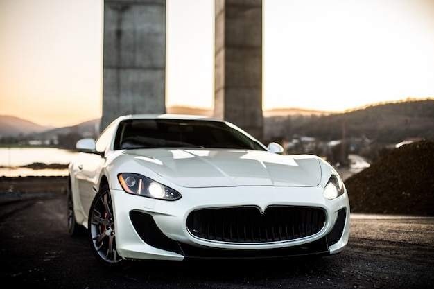 Weißer coupésportwagen, der auf der straße, vorderansicht steht. Kostenlose Fotos