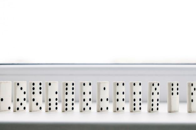 Weißer domino, dominoprinzip, auf weißem hintergrund Premium Fotos