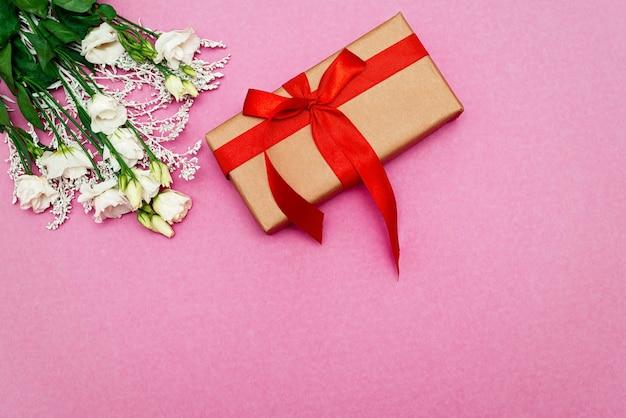Weißer eustoma blumen und geschenkbox rosa hintergrund. muttertag, geburtstag, valentinstag, frauentag, feierkonzept. weicher selektiver fokus. speicherplatz kopieren. Premium Fotos