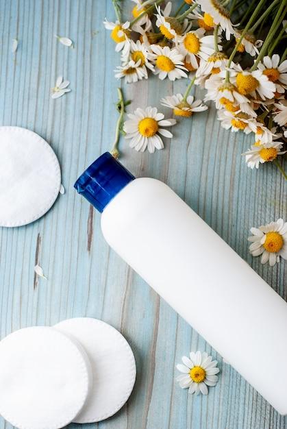Weißer flaschenbehälter mit kräuterkamillenblumen. Premium Fotos