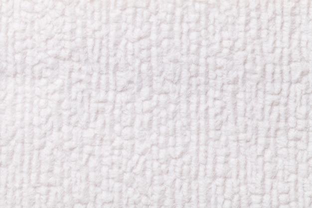 Weißer flauschiger hintergrund aus weichem, flauschigem stoff. beschaffenheit der textilnahaufnahme. Premium Fotos