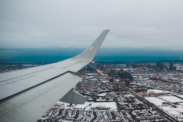 Weißer flugzeugflügel über stadt während des tages Kostenlose Fotos