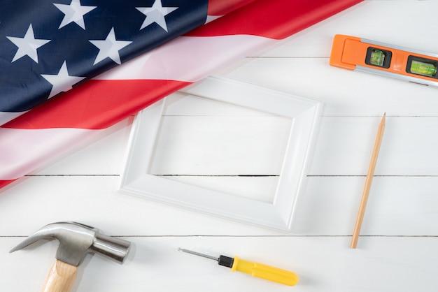 Weißer fotorahmen und amerikanische flagge auf weißem holz Premium Fotos