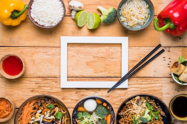 Weißer grenzrahmen mit essstäbchen und thailändischem traditionellem lebensmittel auf hölzernem schreibtisch Kostenlose Fotos