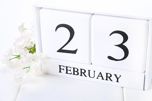 Weißer hölzerner kalender mit schwarzem wort 23. februar mit uhr und anlage auf weißer hölzerner tabelle. Premium Fotos