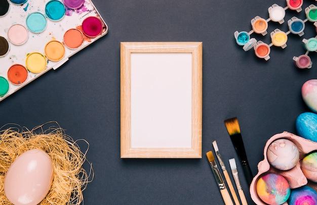 Weißer holzrahmen mit aquarellfarbe; pinsel und osterei auf schwarzem hintergrund Kostenlose Fotos
