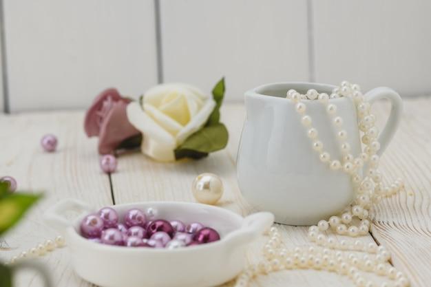 Weißer holztisch mit rosa blumen, bändern und perlen. hochzeits-stil Premium Fotos