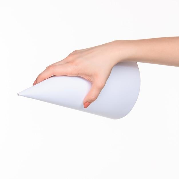 Weißer kegel der requisiten in den weiblichen händen auf weiß mit rechtem schatten Kostenlose Fotos