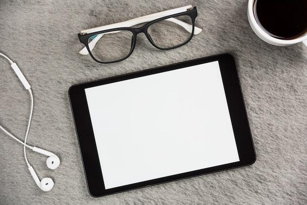 Weißer kopfhörer; brille; kaffeetasse und digitale tablette des leeren bildschirms auf grauem schreibtisch Kostenlose Fotos