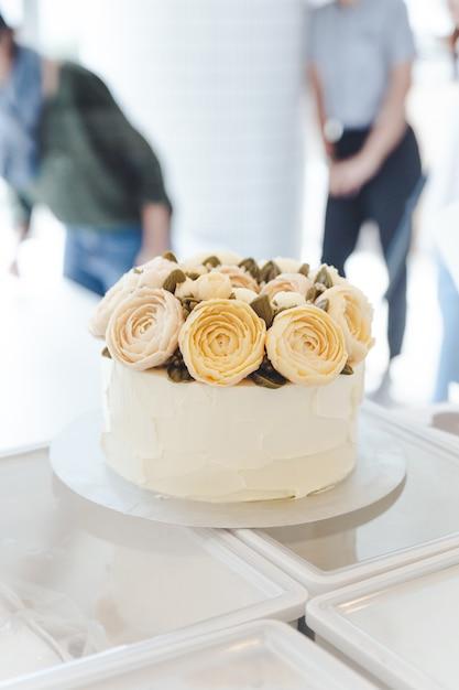Weißer kuchen mit buttercremeblumen verziert auf stand. Premium Fotos