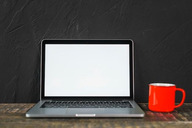 Weißer laptop des leeren bildschirms und rote kaffeetasse über dem holztisch Kostenlose Fotos