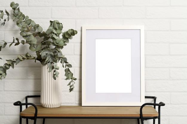 Weißer leerer rahmen auf regal mit pflanze in der vase Premium Fotos