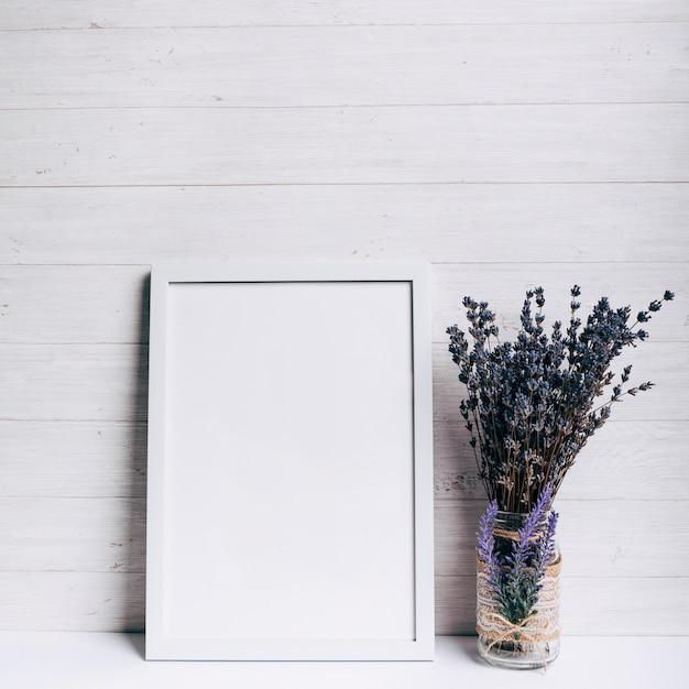 Weißer leerer rahmen nahe dem lavendelglasvase auf weißem schreibtisch gegen hölzernen hintergrund Kostenlose Fotos