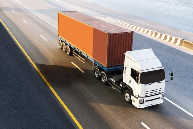 Weißer lkw auf landstraße straße mit rotem behälter, logistischer transport auf der asphaltautobahn Premium Fotos