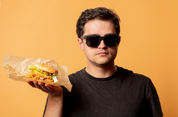 Weißer mann im schwarzen t-shirt mit burger auf gelber wand Premium Fotos