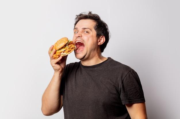 Weißer mann im schwarzen t-shirt mit burger auf weißer wand Premium Fotos
