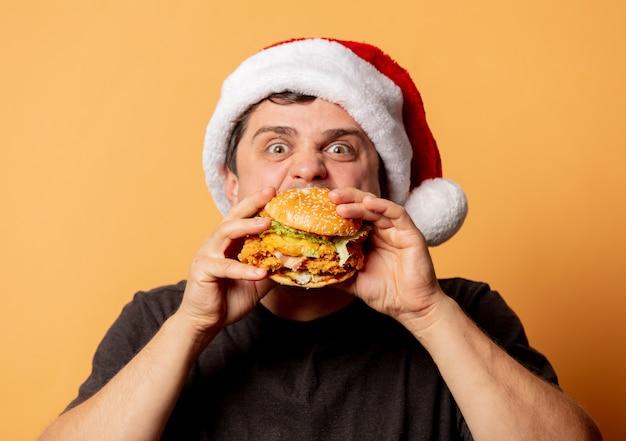 Weißer mann im schwarzen t-shirt und im weihnachtsmannhut mit burger auf gelber wand Premium Fotos