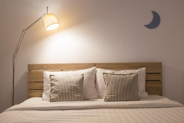 Weißer netter schlafzimmerinnenraum mit lampe und hölzern in der nachtzeit. Premium Fotos