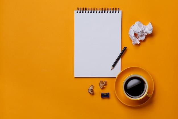 Weißer notizblock auf gelbem hintergrund mit bleistift und papier Premium Fotos
