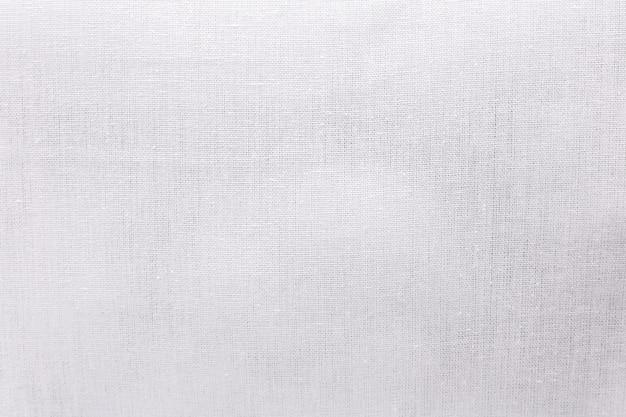 Weißer ökologiestoff-beschaffenheitshintergrund. unbelegtes segeltuchtextilmaterial oder kalikotuch. Premium Fotos