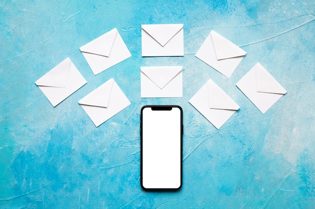 Weißer papierumschlag der mitteilungsikonen über mobiltelefon auf blauem strukturiertem hintergrund Kostenlose Fotos