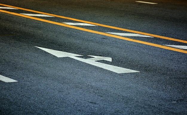 Weißer pfeil und rechts abbiegen auf schwarzem asphalt Premium Fotos