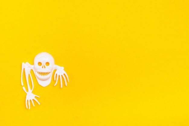 Weißer plastikschädel mit den knochen auf einem gelben papphintergrund. bereite halloween-illustration. kopieren sie platz Premium Fotos