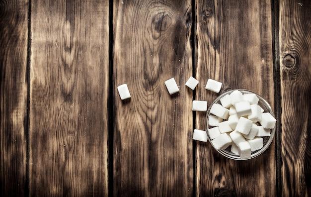 Weißer raffinierter zucker in der tasse. auf holztisch. Premium Fotos