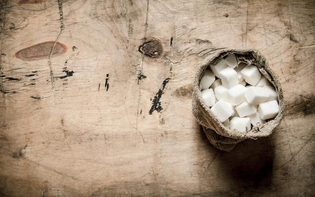 Weißer raffinierter zucker in der tüte. auf dem hölzernen hintergrund. Premium Fotos