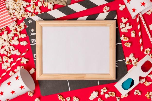Weißer rahmen über der klappe mit popcorn; trinkhalme und 3d-brille auf rotem hintergrund Kostenlose Fotos